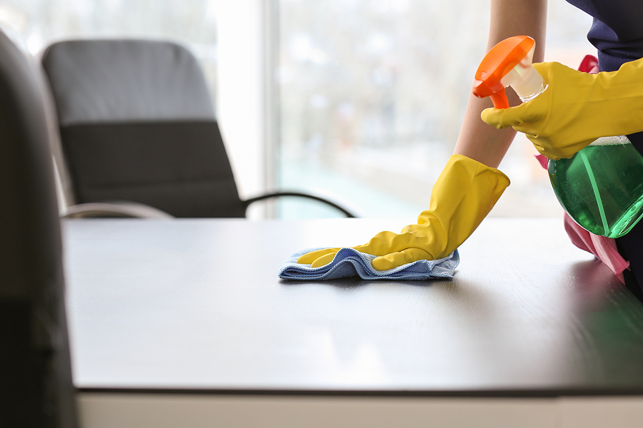 Professional office cleaner in Sydney cleaning a table